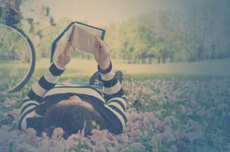 Asian woman reading booklet on the grass. Vintage style.