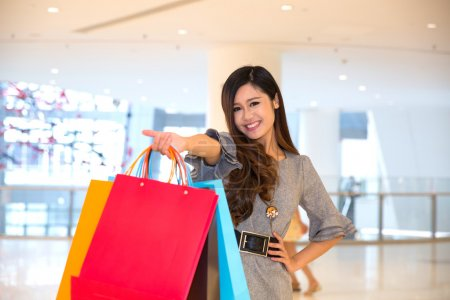 Photo for Young woman carrying shopping bags and smiling in mall - Royalty Free Image