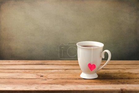 Photo pour Tasse de thé avec forme de coeur sur la table en bois - image libre de droit