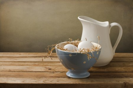Fresh eggs with white jug on wooden table