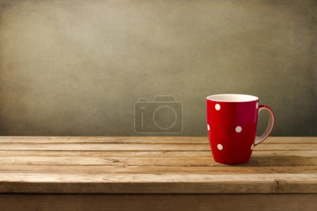Photo for Red cup with dots on wooden table over grunge background - Royalty Free Image
