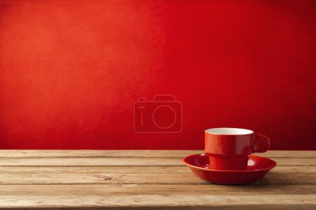 Photo for Red coffee cup on wooden table over red grunge background - Royalty Free Image