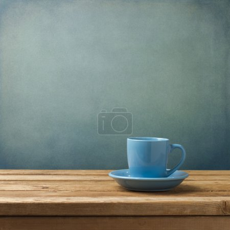 Photo for Blue coffee cup on wooden table over blue grunge background - Royalty Free Image