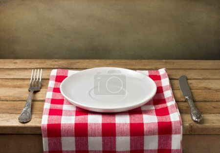 Photo for Empty plate on wooden table over grunge background - Royalty Free Image