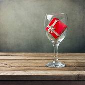 Sklenice na víno s červené krabičky na dřevěný stůl
