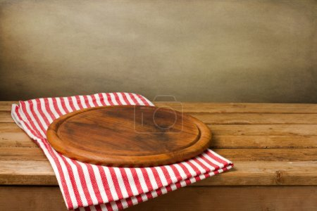 Photo for Wooden board stand on tablecloth over grunge background - Royalty Free Image