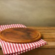 Wooden board stand on tablecloth over grunge backg...