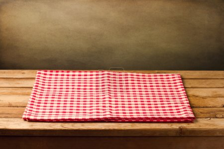 Empty table with tablecloth over grunge background