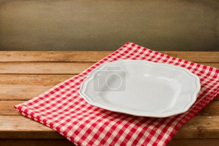 Empty white plate on tablecloth on wooden vintage table