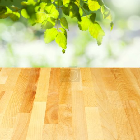 Empty wooden table over leaves bokeh background