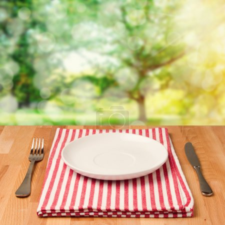 Photo for Empty plate with silverware on wooden table over bokeh background - Royalty Free Image