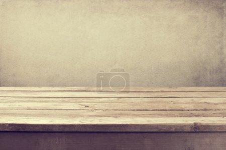 Photo pour Fond vintage avec table de terrasse en bois et mur grunge lumineux - image libre de droit