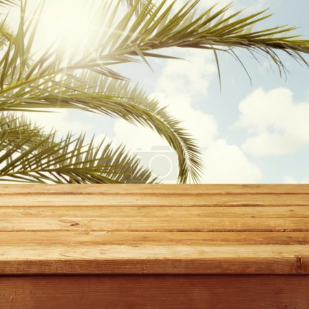 Empty wooden deck table over palm tree branches