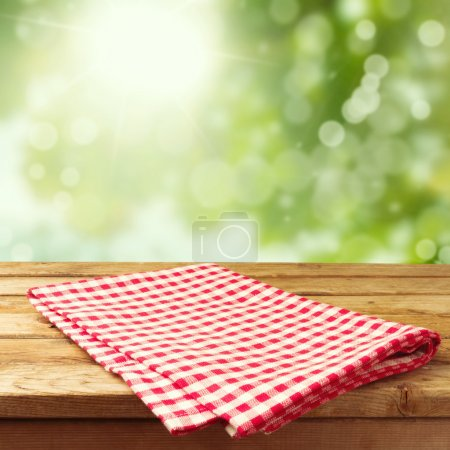 Photo for Empty wooden deck table with tablecloth over bokeh background - Royalty Free Image