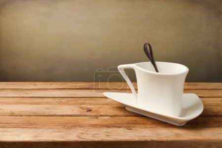 Photo for White coffee cup on wooden table over grunge background - Royalty Free Image