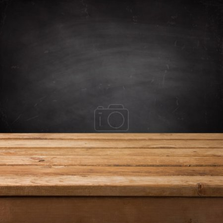 Empty wooden deck table over chalkboard...
