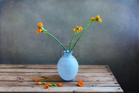 Photo pour Fleurs orange dans un vase bleu sur une table de pont en bois sur fond grunge - image libre de droit