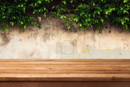 Photo for Wooden deck table over urban wall with leaves - Royalty Free Image
