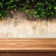 Wooden deck table over urban wall with leaves...