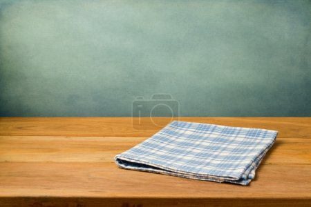 Photo for Wooden table with tablecloth over grunge blue wall - Royalty Free Image