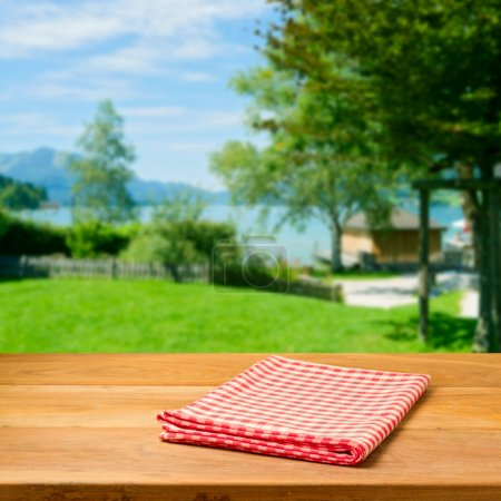 Photo for Empty wooden table with checked tablecloth over beautiful landscape. Perfect for product montage. - Royalty Free Image