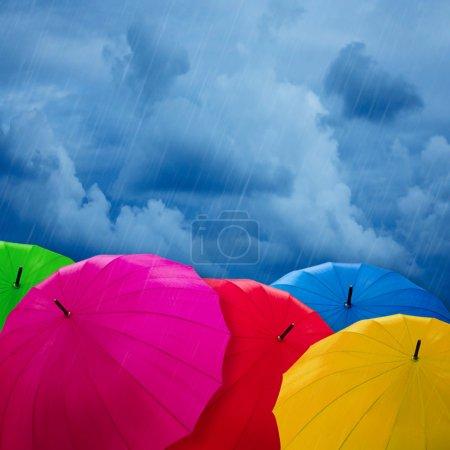 Foto de Coloridos paraguas sobre cielo nublado. concepto de mal tiempo - Imagen libre de derechos
