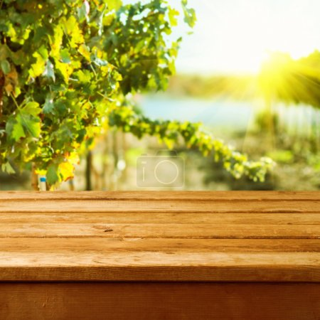 Photo for Empty wooden deck table over vineyard bokeh background - Royalty Free Image