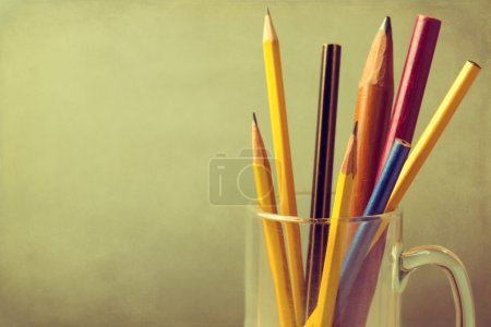 Close up of vintage pencils in glass over grunge background with copy space
