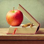 Régi könyv és az apple, a fából készült asztal fölött grunge háttér. Vissza a concept iskolai