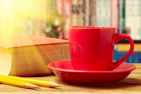 Red coffee cup with books and pencils