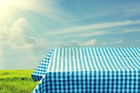 Empty table covered with blue checked tablecloth over beautiful sky. Ready for product montage