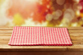 Empty wooden table with red checked tableclo