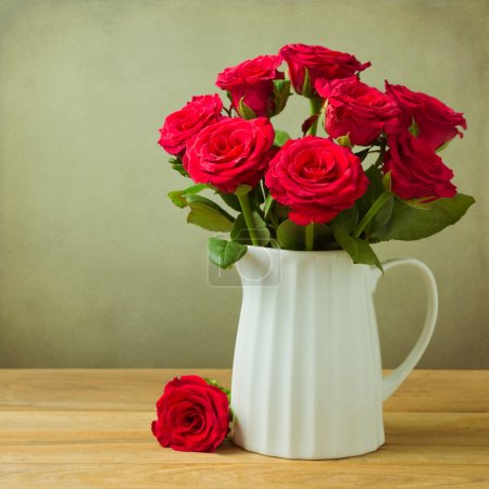 Photo for Rose flower bouquet in jug on wooden table - Royalty Free Image