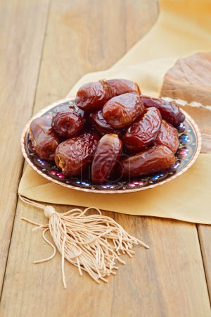 Dates on plate over wooden background