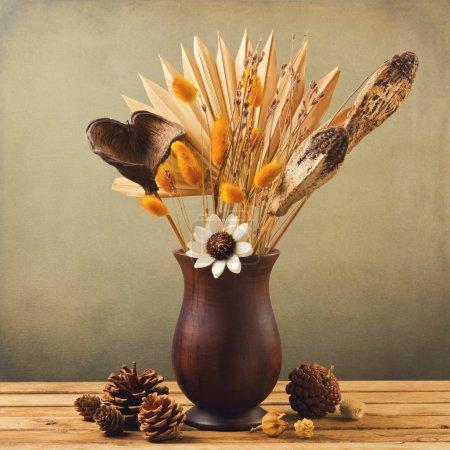 Photo pour Fleurs séchées dans un vase en bois avec pin sur fond grunge - image libre de droit