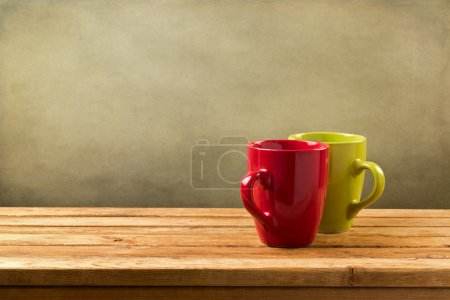 Photo for Coffee cups on wooden table over grunge background - Royalty Free Image