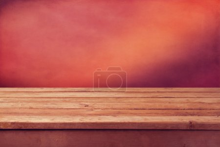Wooden table over red background
