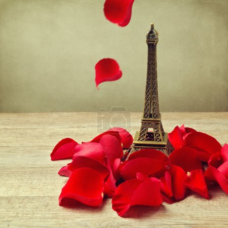 Photo for Small Eiffel tower with roses petals on wooden table - Royalty Free Image