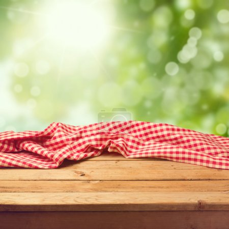 Photo for Empty wooden deck table with tablecloth over green bokeh background - Royalty Free Image