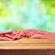 Empty wooden deck table with tablecloth over natur...