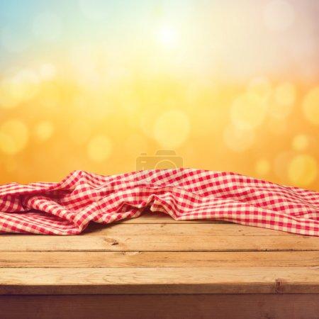 Photo pour Table de terrasse en bois vide avec nappe coucher de soleil fond bokeh - image libre de droit