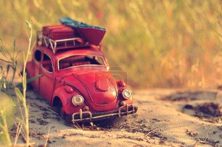 Toy car with luggage on sandy beach