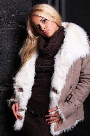 Photo pour Belle femme blonde dans une fourrure près de mur de briques - image libre de droit