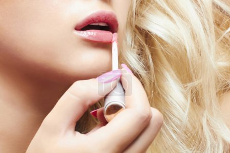 Beautiful blond woman paints lips with lipstick. lip gloss