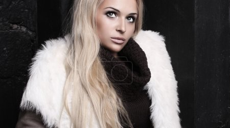 Beautiful blond woman in fur near bricks wall. winter fashion. fur coat. make-up