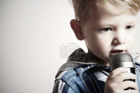 Photo pour Portrait du petit garçon, chantant dans un micro. enfant en karaoke.fashion - image libre de droit