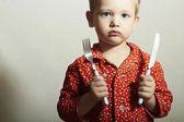 Hezký chlapeček s vidličkou a nožem. hladové dítě. Krása a jídlo. Chci jíst