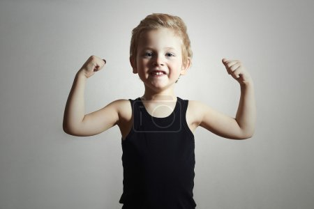 Child. Funny Little Boy.Sport Handsome Boy.showing his hand biceps muscles