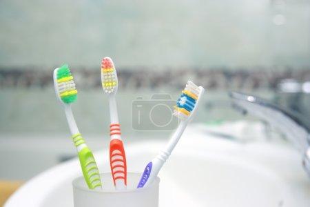 Photo pour Trois brosses à dents dans une salle de bain. Gros plan sur la brosse à dents . - image libre de droit
