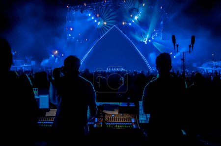 Photo for Large crowd looking towards empty stage with sound engineers and mixing desk in foreground - Royalty Free Image